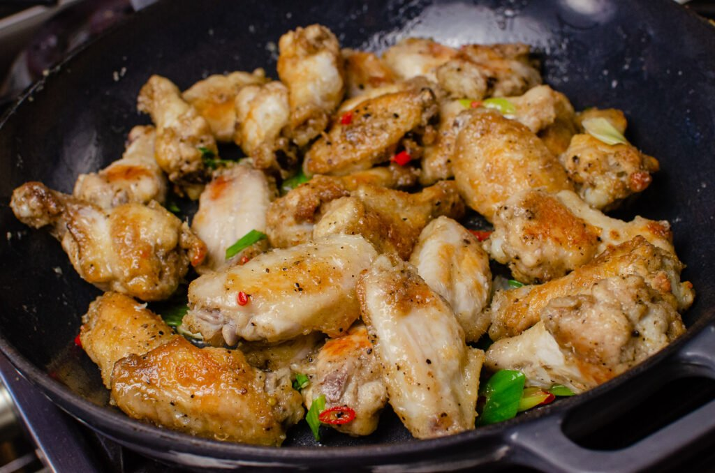 Chickne wings in a cast iron dish cooking with the chopped spring onions and chopped chilli