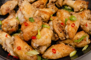 salt and pepper chicken wings garnished with chopped spring onion and chopped red chilli in a cast iron pan