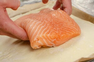 Placing a salmon fillet onto a puff pastry sheet by hands
