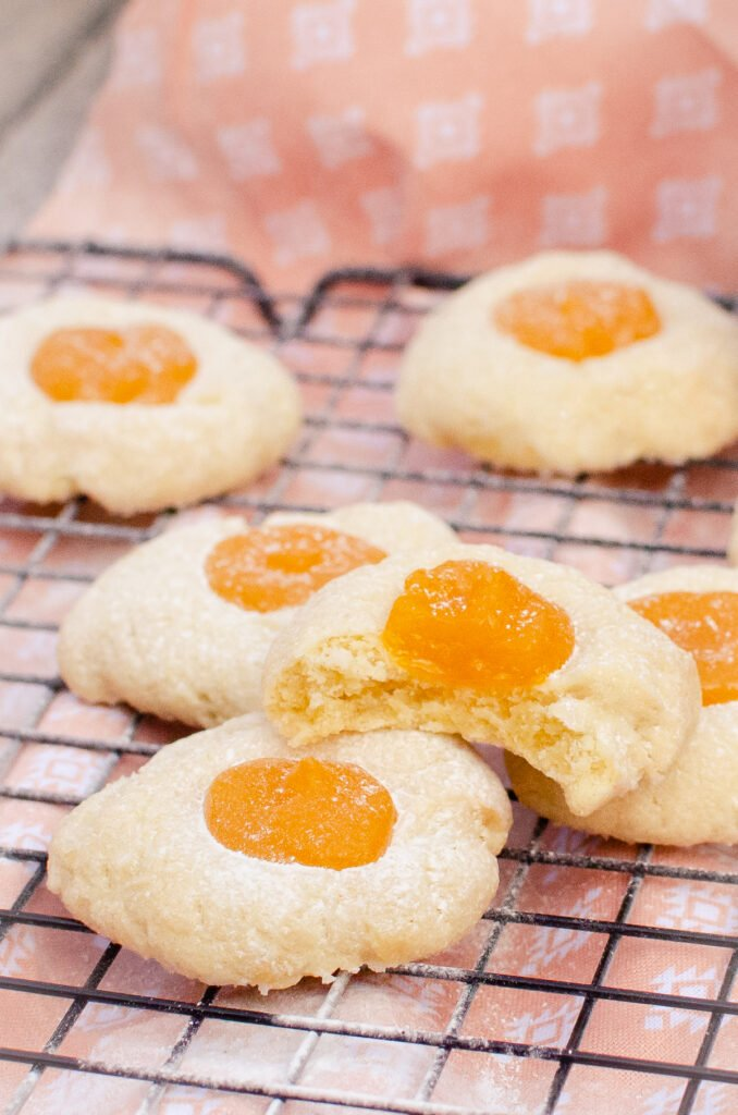 Passion fruit curd thumbprint cookies sprinkled with icing sugar and a bite taken out of one.