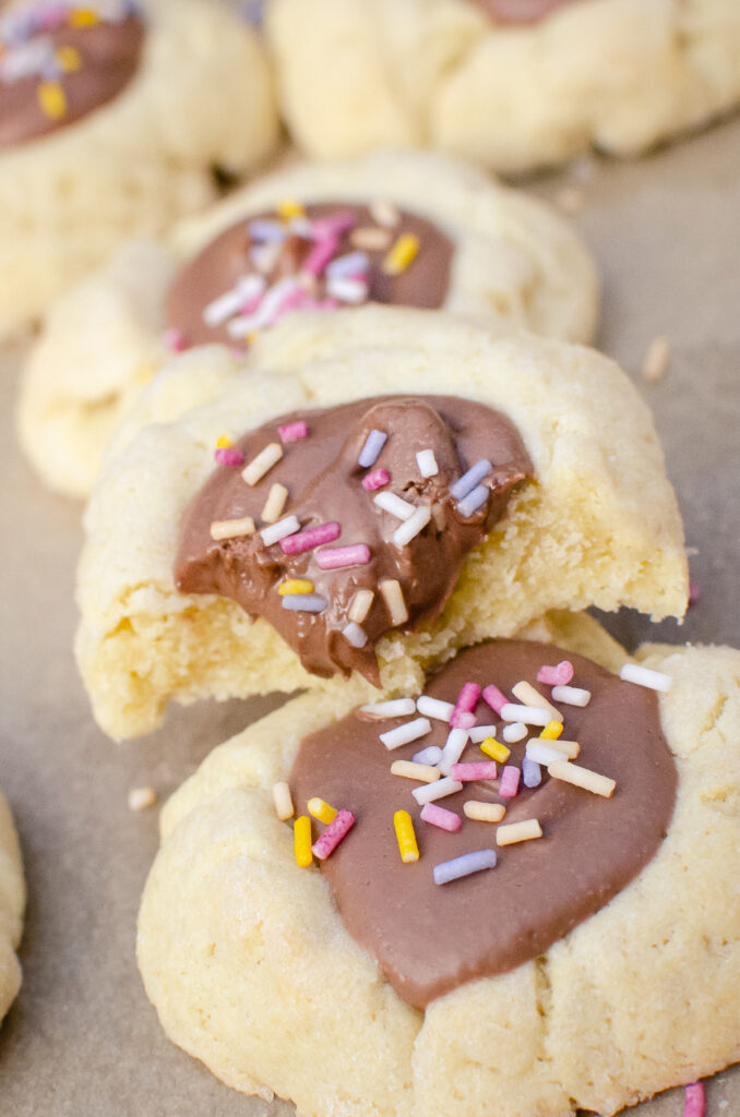 Sprinkle covered chocolate thumbprint cookies stacked on top of each other, with 2 bites taken out of one.