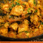 Pin image of our Chicken Bhuna Curry being scooped up with a wooden spoon