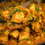 Chicken Bhuna Curry being scooped up with a wooden spoon