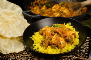 Chicken Bhuna Curry served with pilau rice in a black bowl with poppadoms on the side