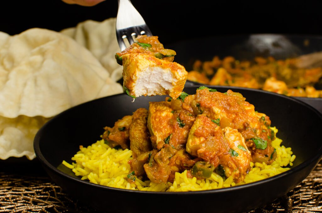 A piece of curry chicken on a silver fork which has been eaten and the bhuna curry in a black bowl served with pilau rice and poppadoms on the side