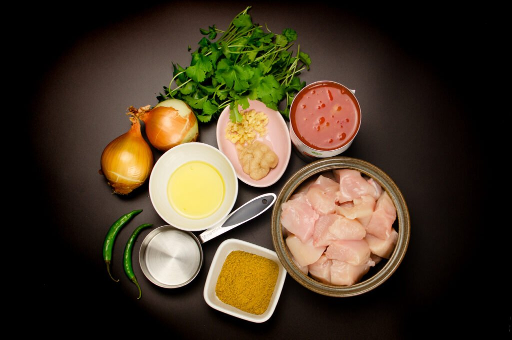 Picture of Ingredients for our Chicken Bhuna Curry which consists of Cut chicken breast,chopped tomatoes, curry powder,garlic puree, ginger,vegetable oil, water ,two green chillies, two onions and fresh coriander