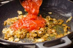 Chopped tomatoes being poured onto chopped onions and curry powder in a cast iron pan