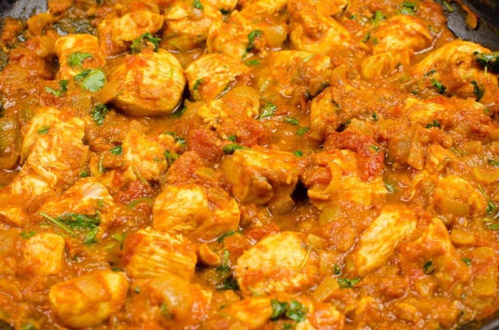 Chicken Bhuna Curry cooking in a cast iron dish