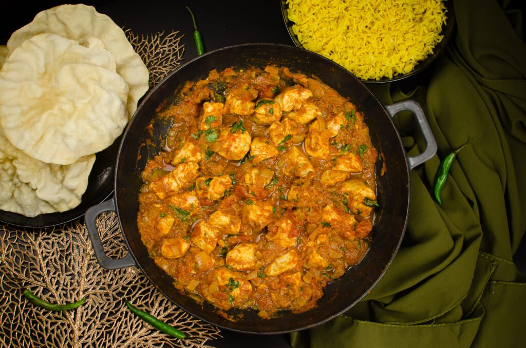 Homemade Chicken Bhuna Curry served in a cast iron pan with poppadoms and pilaf rice on the sides