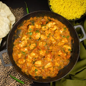 Takeaway style Chicken Bhuna Curry served in a cast iron pan with poppadoms and pilaf rice on the sides
