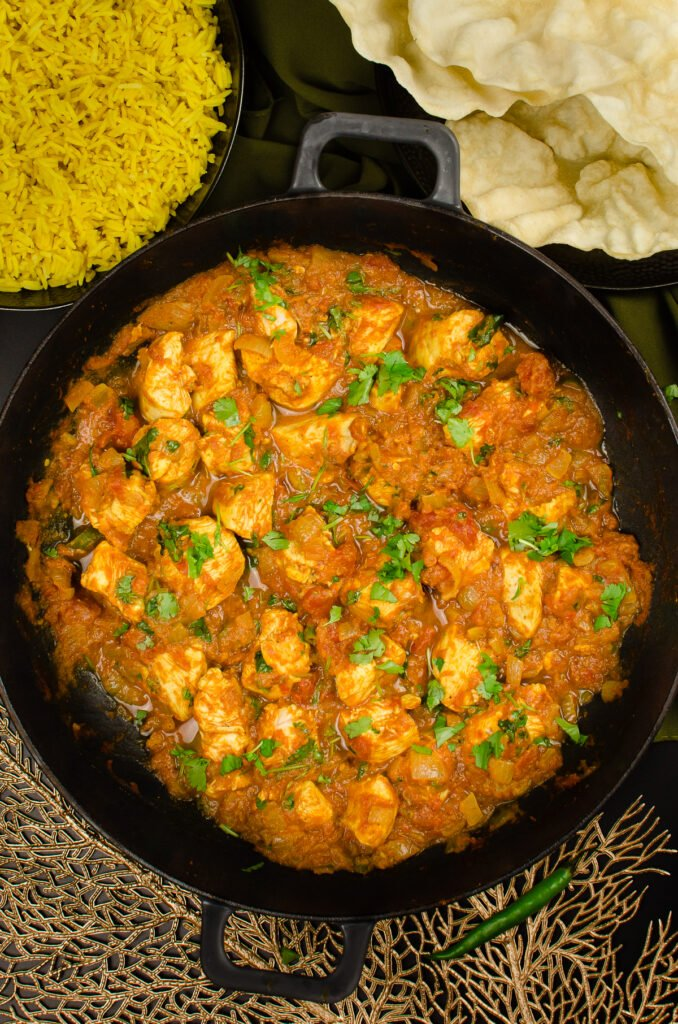 Indian Takeaway style Chicken Bhuna Curry served in a cast iron pan with poppadoms and pilaf rice on the sides