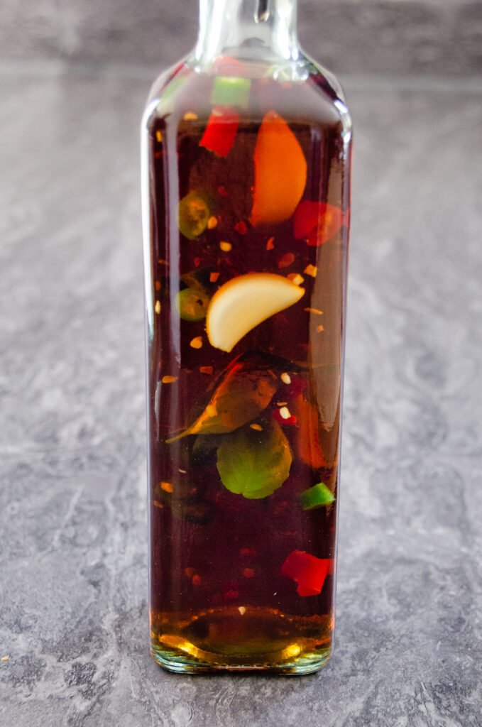 A bottle of chilli vinegar filled up with chopped green chillies, red chillies, three garlic cloves and fresh basil inside