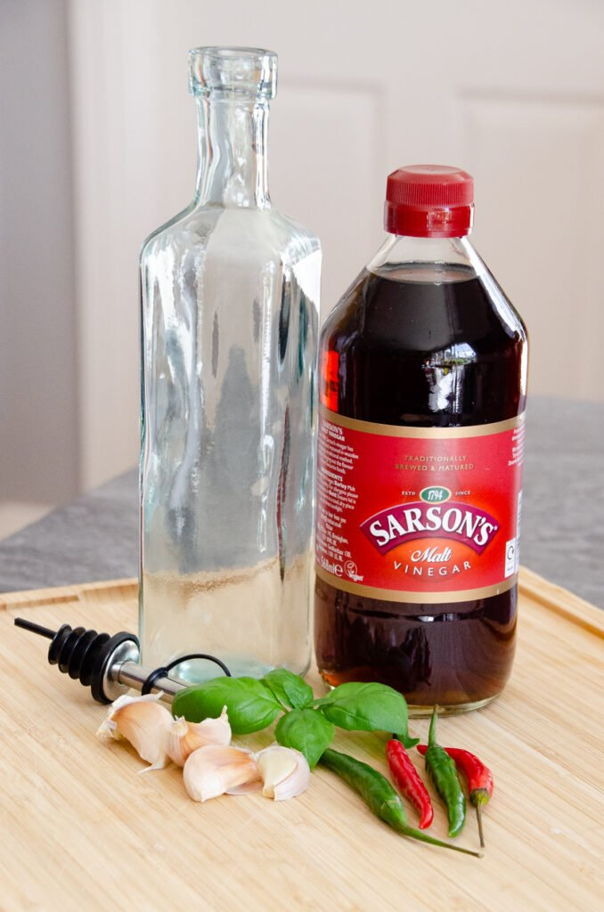A bottle of Sarsons vinegar, a clear glass empty bottle, fresh basil, garlic cloves green and red chilies on a wooden board