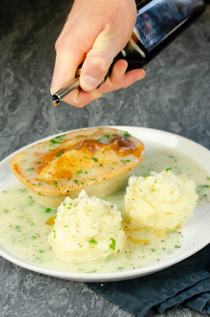 Drizzling our home made chilli vinegar by hand over pie, mash and liquor served on a round white plate