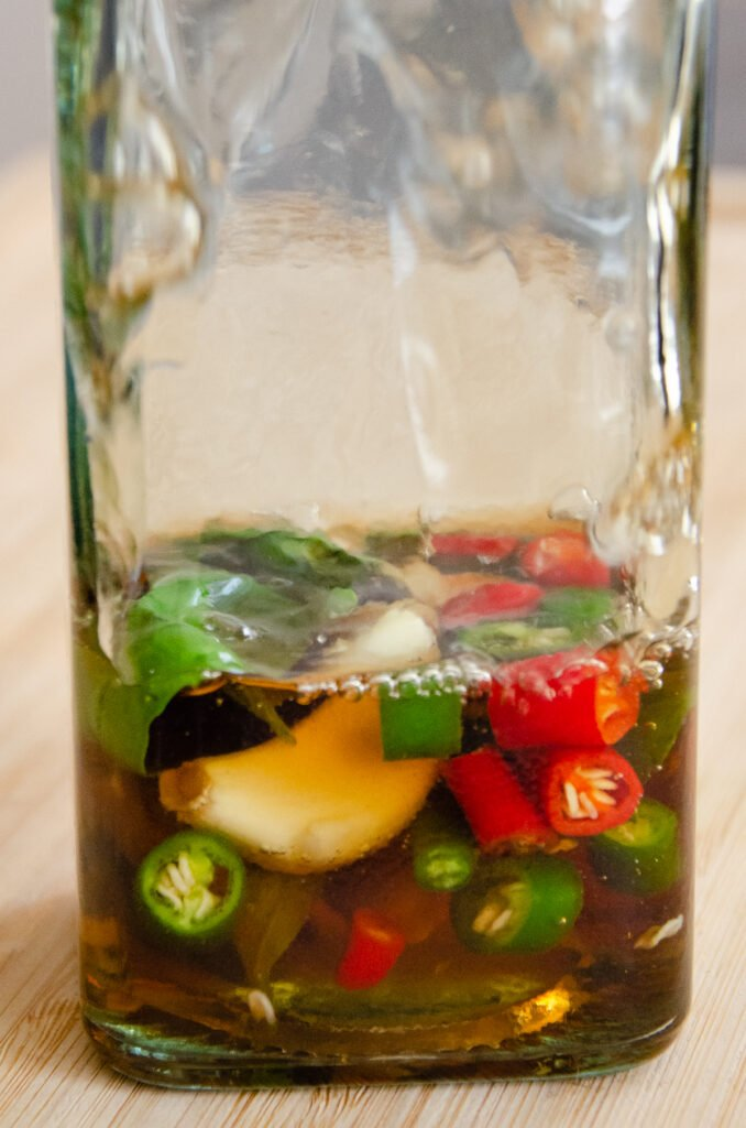 A clear glass bottle being filled with vinegar bottle with chopped green chillies, red chillies, three garlic cloves and fresh basil inside
