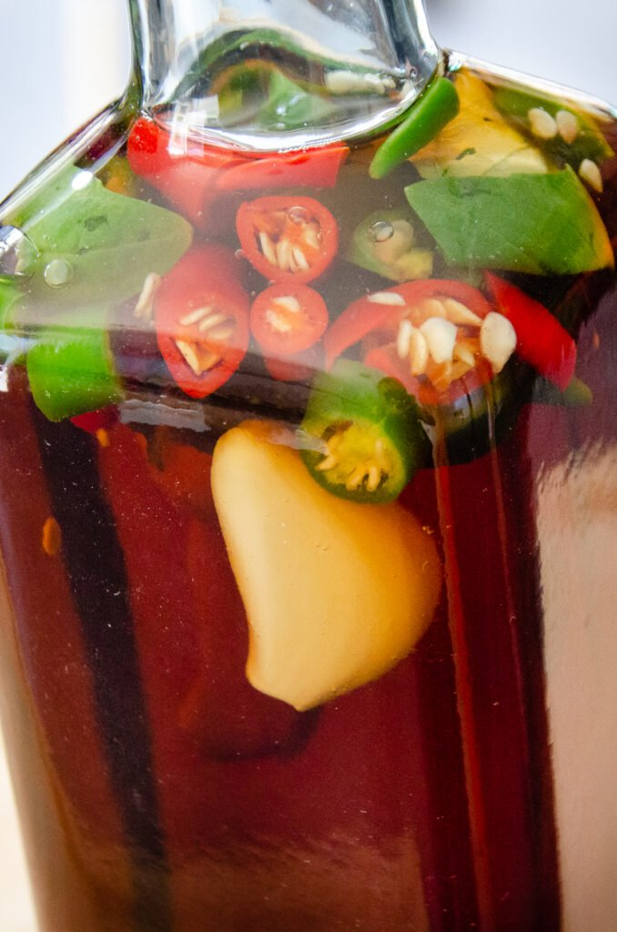 Chilli vinegar filled up with chopped green chillies, red chillies, three garlic cloves and fresh basil inside