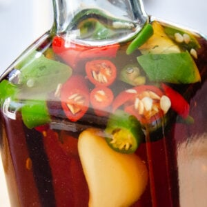 A close up picture of our chilli vinegar with fresh green and red chillies, garlic cloves and fresh basil inside the bottle