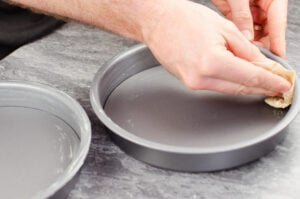 Greasing two cake tins by hand with butter on parchment paper