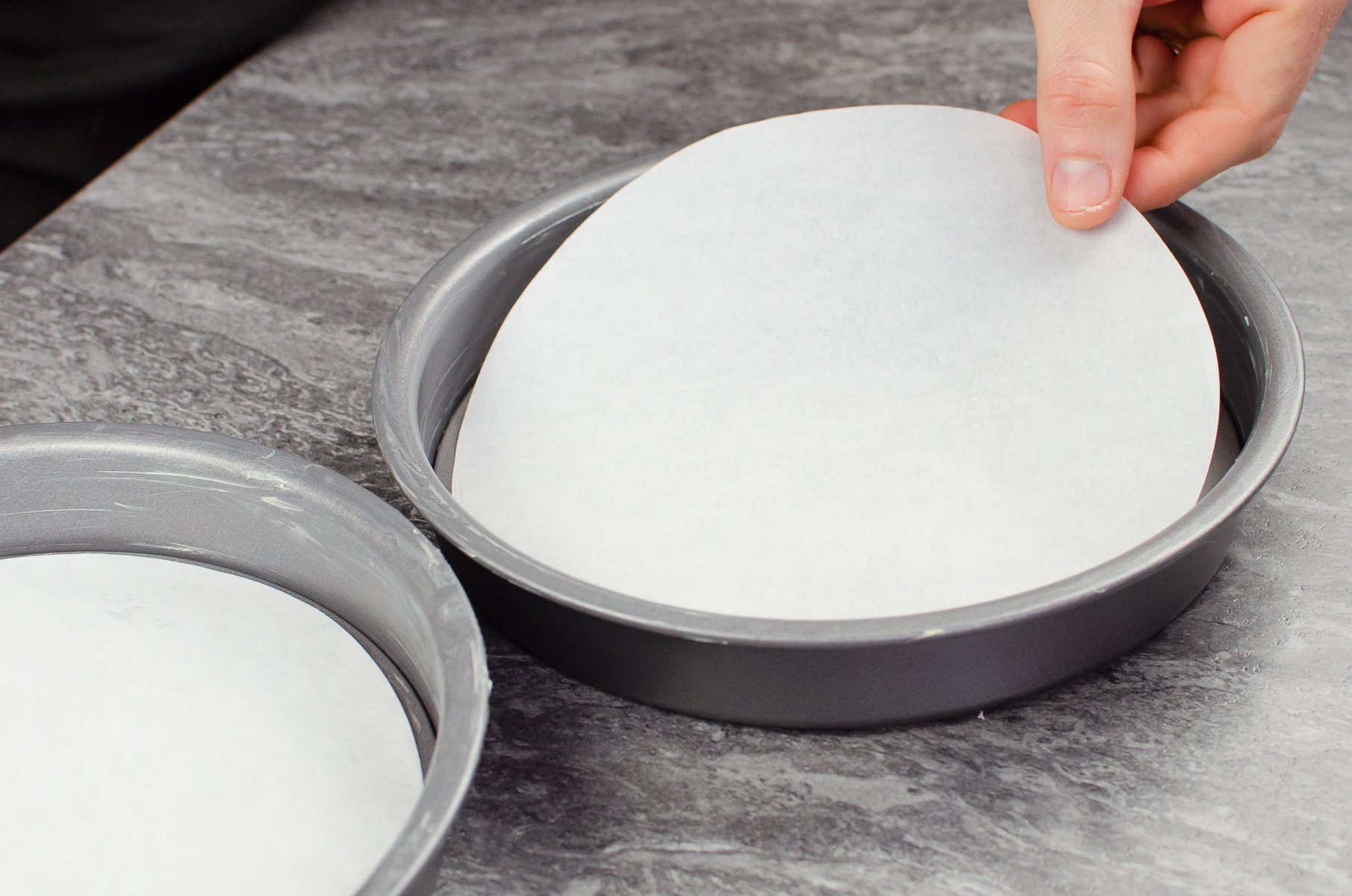 Placing parchment paper cake liners in the bottom of the two cake tins
