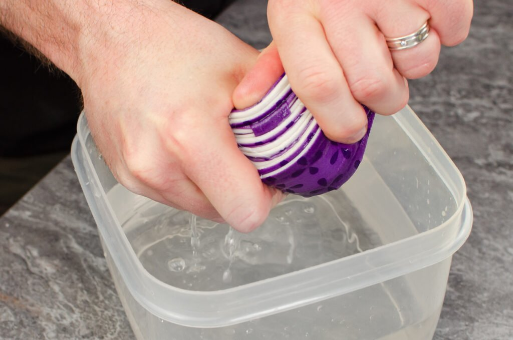 Squeezing the water away from the baking strips by hand over a clear plastic bowl filled with water