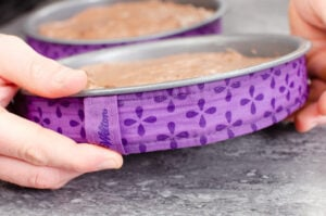 Placing Wilton baking strips around two cake tins by hand filled with chocolate cake mixture