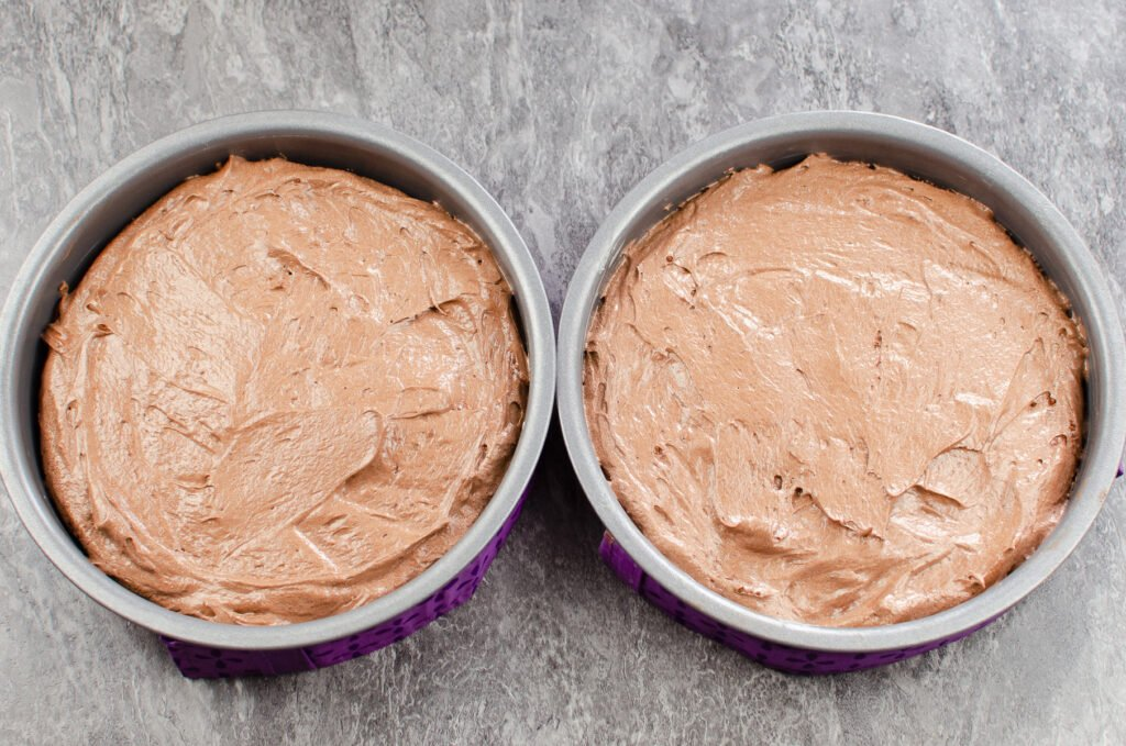 Two cake tins filled with chocolate cake mix