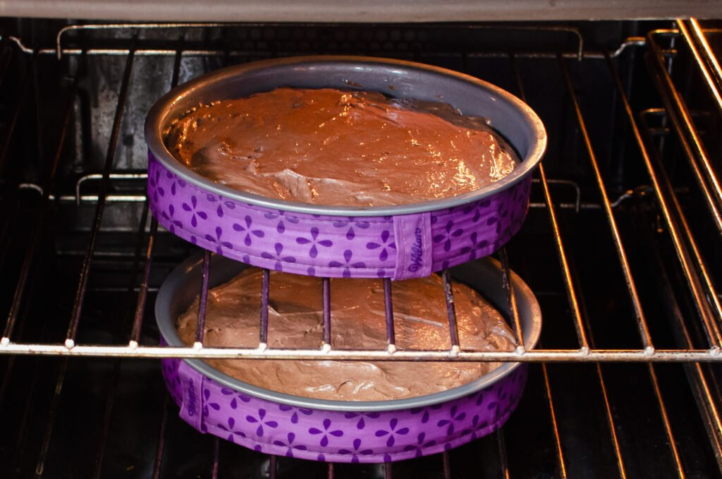 Two sandwich cake tins filled with chocolate cake mix with baking strips on the outside placed in an oven to cook