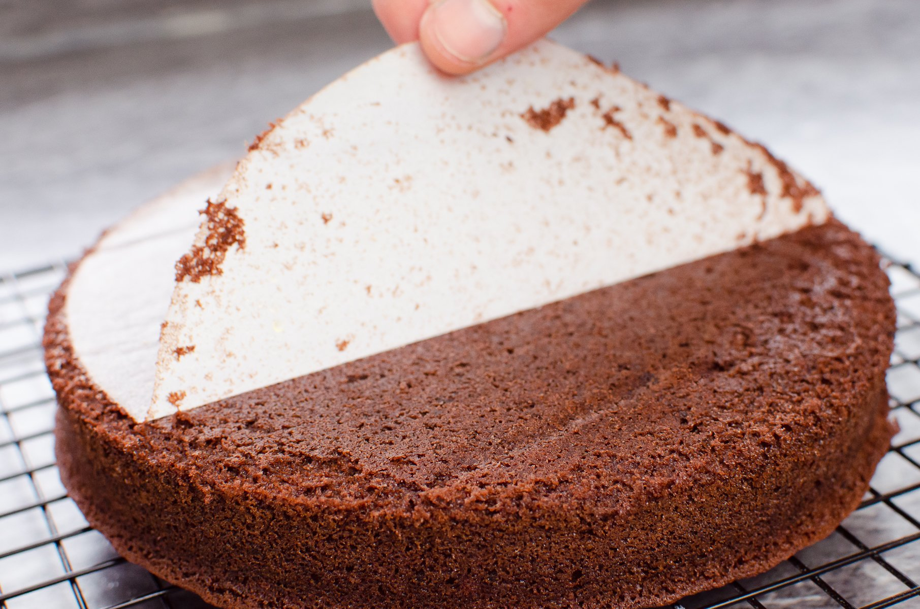Removing the cake tin parchment paper liner away from the chocolate cake which is cooling on a wire rack