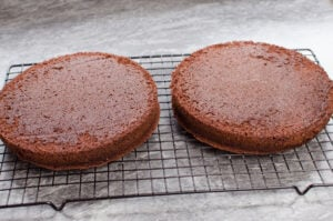 Two chocolate sponges cooling on a black wire rack