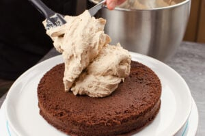 Chocolate frosting being placed onto a bottom chocolate cake base with a black spatula and silver knife