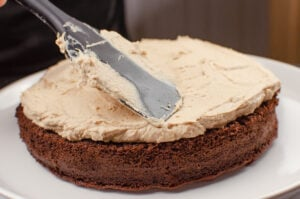 Flatting down the chocolate cake filling with a black spatula