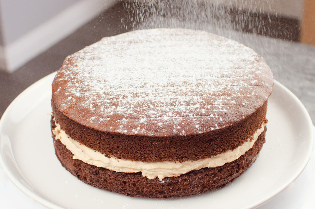 Sprinkling icing sugar over the top of a Chocolate Victoria Sponge Cake served on a white plate