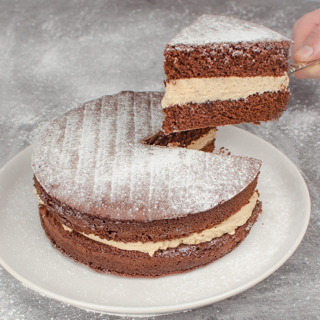 Holding up a slice of our Chocolate Victoria Sponge Cake by hand with a silver cake knife and the chocolate cake on a white plate with icing sugar sprinkled all over the surface