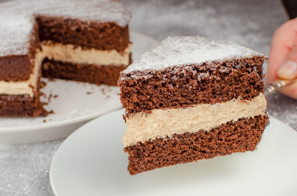 Holding up a slice of our Chocolate Victoria Sponge Cake by hand with a silver cake knife