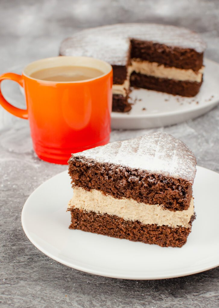 Slice of chocolate Victoria sponge cake with chocolate buttercream served on a white plate. With the remaining cake behind and a orange mug of tea.