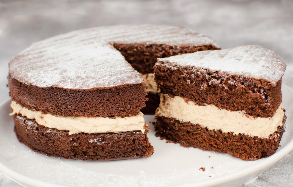 Chocolate Victoria Sponge Cake with a slice cut out served on a white plate. With a orange mug of tea.