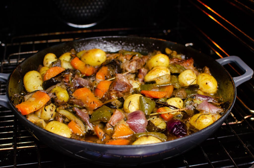 Cooked Croatian Lamb Peka in a cast iron pan in the oven