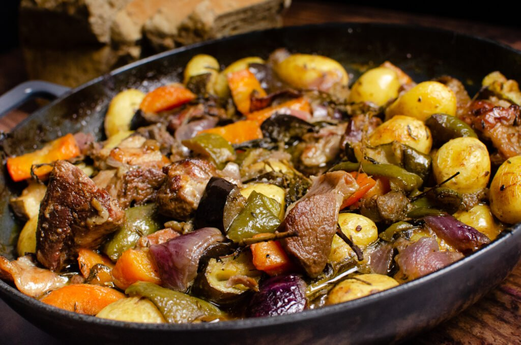 Croatian Lamb Peka consisting of lamb chunks, potatoes, chopped aubergine, courgette, red onion, carrots, green peppers, thyme, rosemary and sage cooked in oil in a cast iron pan