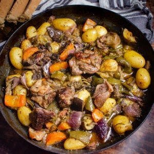 Traditional Croatian Lamb Peka consisting of lamb chunks, potatoes, chopped aubergine, courgette, red onion, carrots, green peppers, thyme, rosemary and sage cooked in oil in a cast iron pan