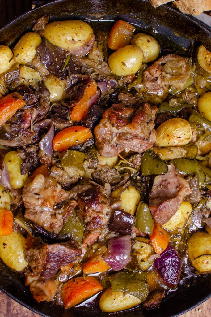 Croatian national dish lamb peka consisting of lamb chunks, potatoes, chopped aubergine, courgette, red onion, carrots, green peppers, thyme, rosemary and sage cooked in oil in a cast iron pan