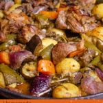 Pin image of our Croatian Lamb Peka consisting of cooked lamb chunks, potatoes, chopped aubergine, courgette, red onion, carrots, green peppers, thyme, rosemary and sage cooked in oil in a cast iron pan