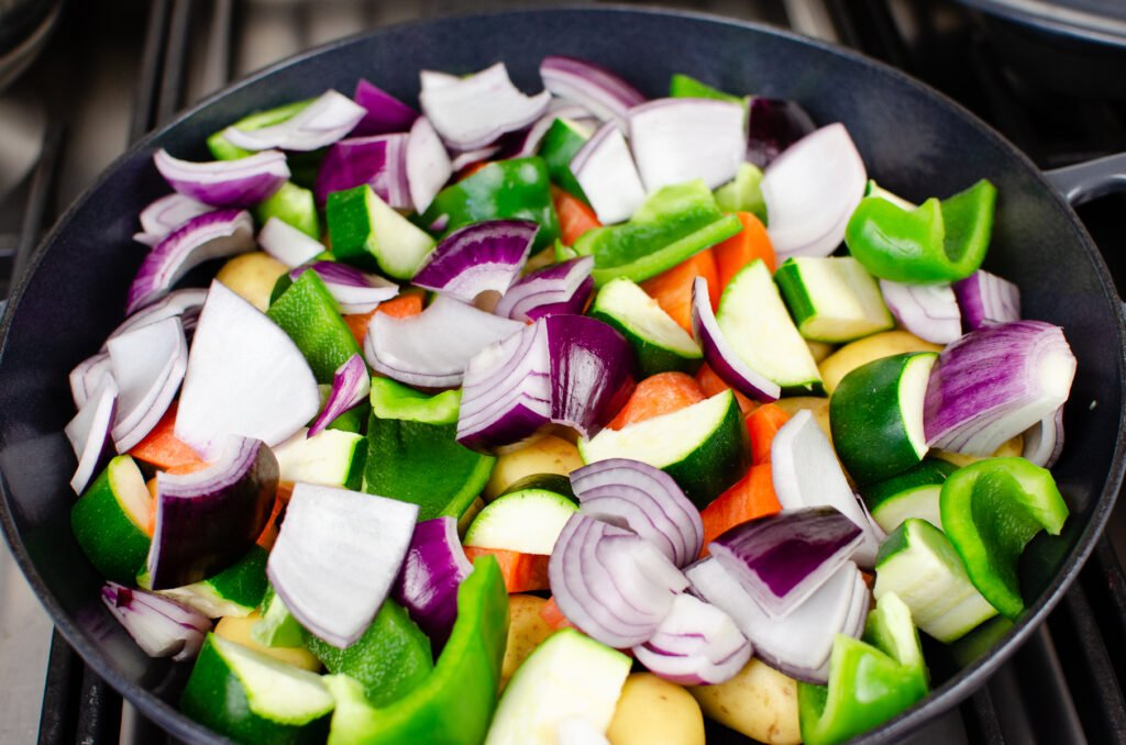 Chopped up vegetables which consist of chopped up red onion, courgette, potatoes red peppers in a cast iron pan
