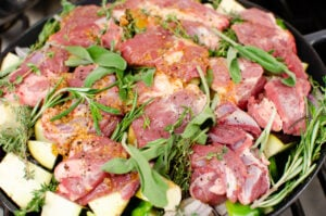Chunks of lamb coated in a sundried tomato oil sauce and covered with thyme, rosemary and sage which is on top of chopped red onion, aubergine, courgette and potatoes in a cast iron pan