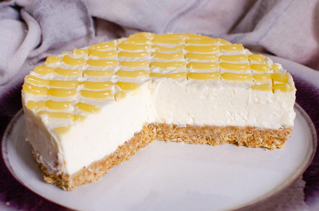 No bake Lemon Curd Cheesecake served on a white plate with a 3rd of the cheesecake cut away