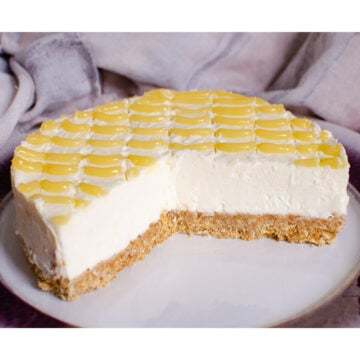 The best Lemon Curd Cheesecake served on a white plate with a 3rd of the cheesecake cut away