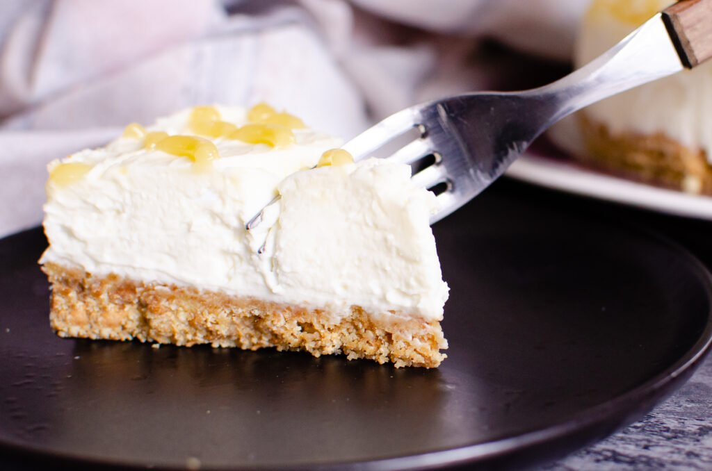 A slice of Lemon Curd Cheesecake on a black plate being eaten with a silver fork