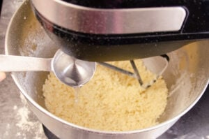 Pouring water from a tablespoon into the shortcrust pastry mixture while being mixed in a electric standing mixer