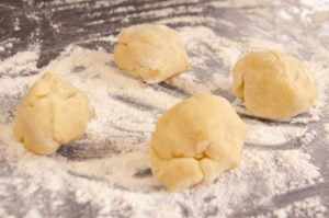 Four balls of shortcrust pastry on a floured surface