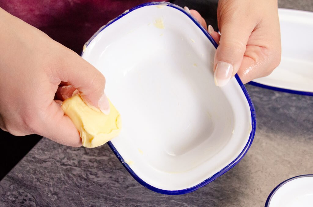 Greasing a pie tin with butter by hand