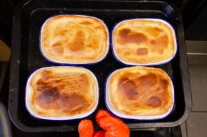 Four mince beef pies cooked on a black baking tray
